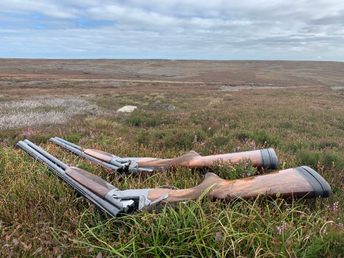 Two shotguns on the heather in front of a grouse butt on the North Yorkshire Moors